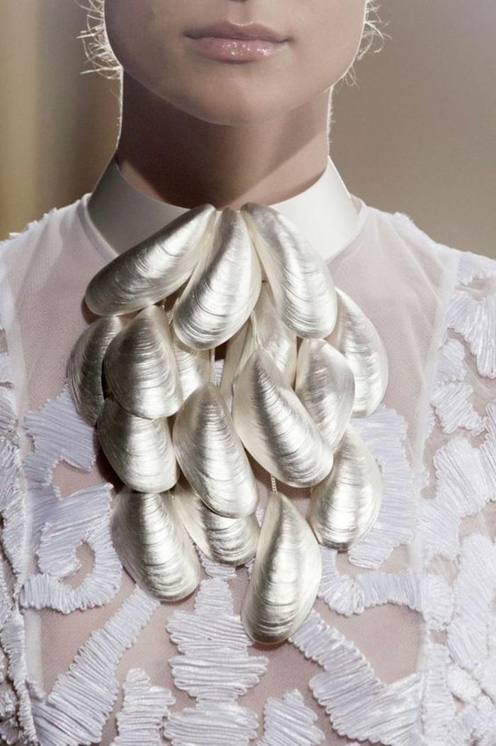 blouse blanche semi transparente avec des ornements en dentelle et avec un collier avec des coquillages couleur argent, tenue chic et choc