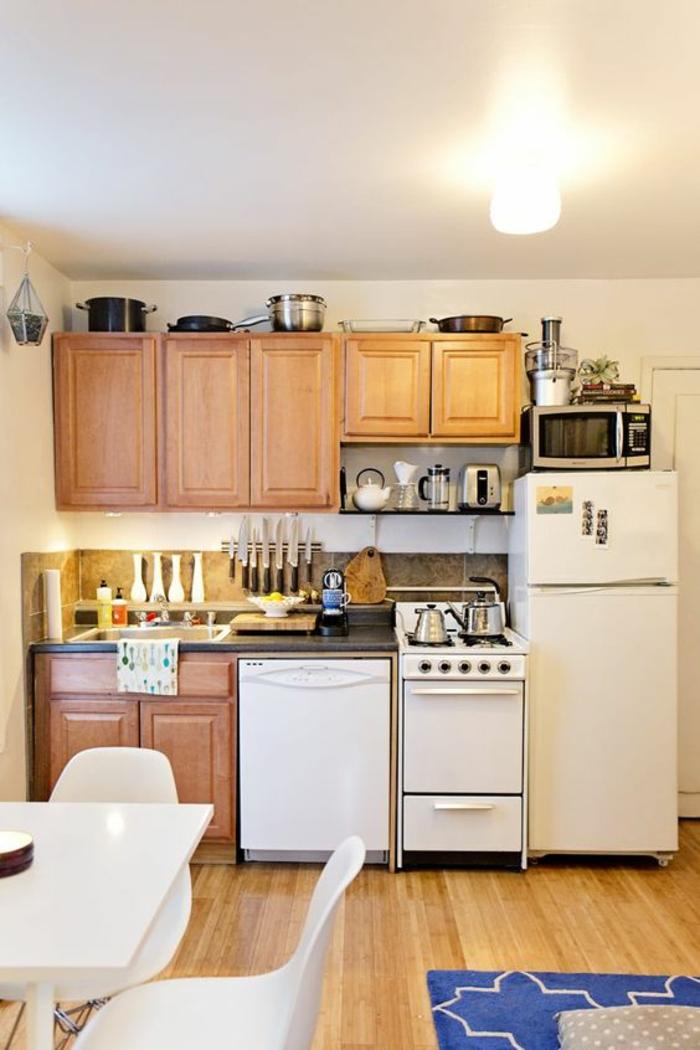 cuisine en longueur, meubles en bois clair et électroménagers en blanc, parquet en bois PVC en nuances jaunes, tapis en bleu électrique, avec des formes géometriques