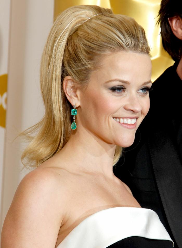 haut ponytail de Reese Witherspoon, boucles d'oreilles pendantes, yeux soulignés