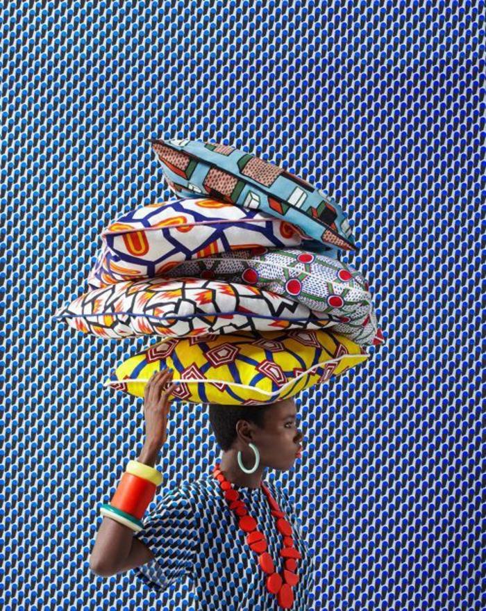 femme avec des coussins aux motifs africains sur la tête, grand collier massif en rouge, bracelets massifs en rouge et jaune, tenue africaine femme