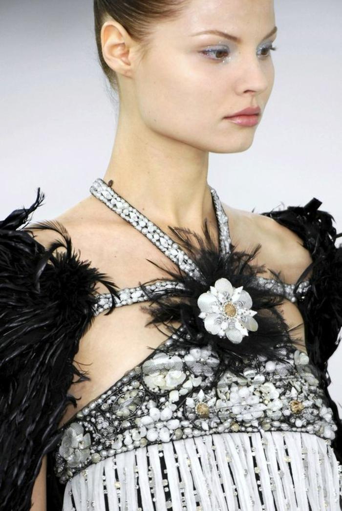 top en noir et blanc, avec grande fleur blanche au milieu du décolleté, des multiples fleurs blanches de taille plus petite au niveau des seins, haut chic bas choc