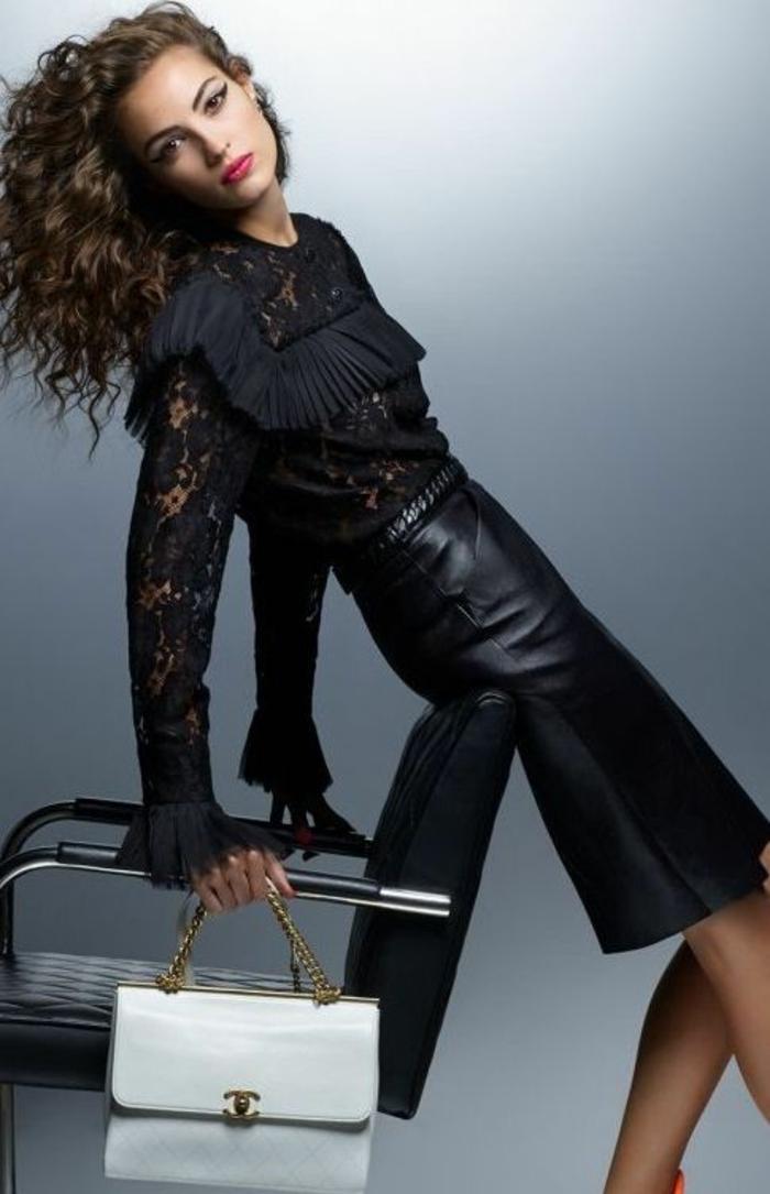 jupe crayon en cuir noir, chic détail choc, blouse avec des volants plissés sur le buste, manches longues en dentelle noire, sac pochette blanc avec chaîne en couleur or