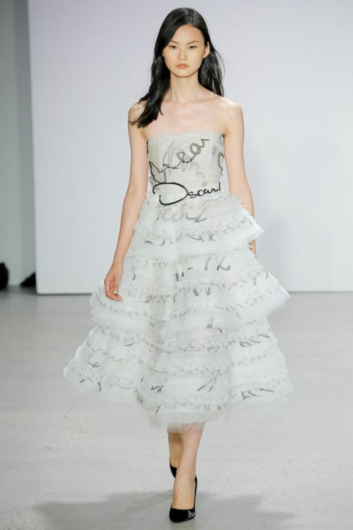 robe bustier blanche avec des grands volants et des inscriptions en noir, tenue chic et choc, escarpins pointus noirs