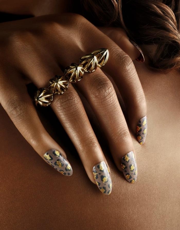 idée pour ongle gel deco de base grise aux dessins design animal en noir et or, modèle de bijou en or pour les doigts