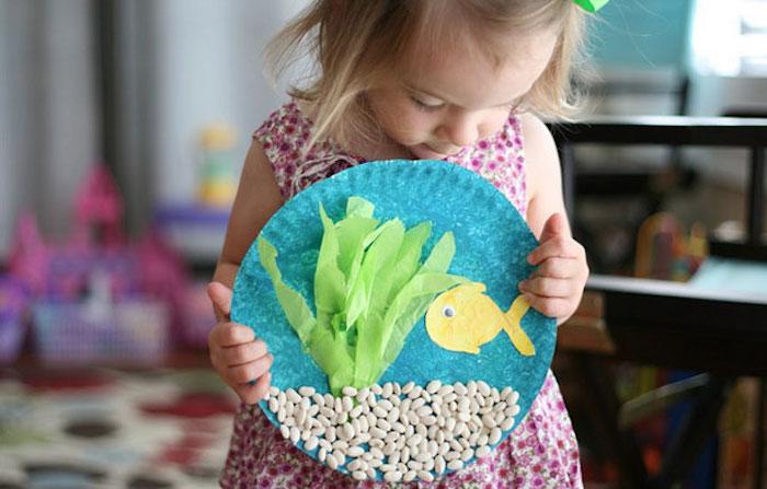 pédagogie montessori en crèche, leçon sur les fond marins, assiette en papier bleue avec décoration de pois blancs, algues en bandes de papier de soie et poisson en papier jaune