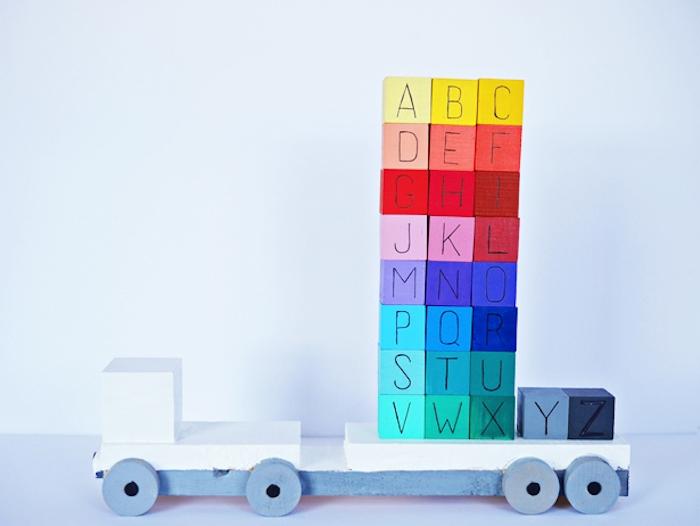 des cubes colorés en bois avec les lettres de l alphabet à ranger sur une plateforme de camion, montessori methode