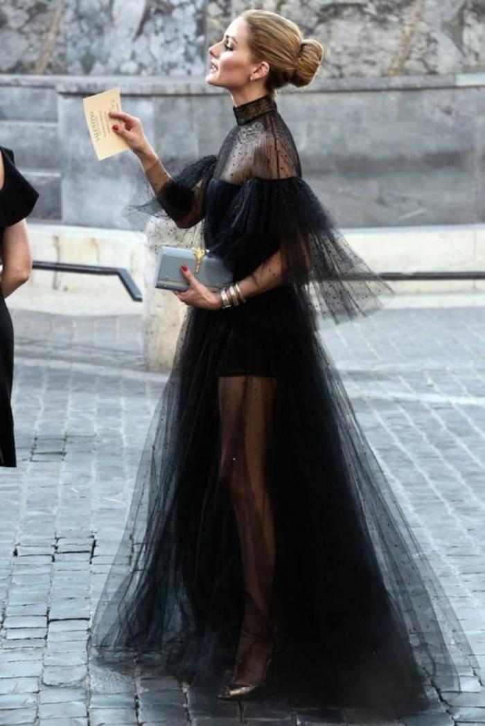 robe en tulle noir avec taffetas, col tortue, zone épaules transparente, manches fortement évasées avec des volants larges, tenue chic et choc