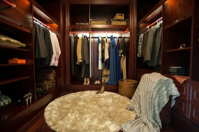 amenagement dressing, un dressing en U cosy avec grand tapis rond, penderies en bois foncé