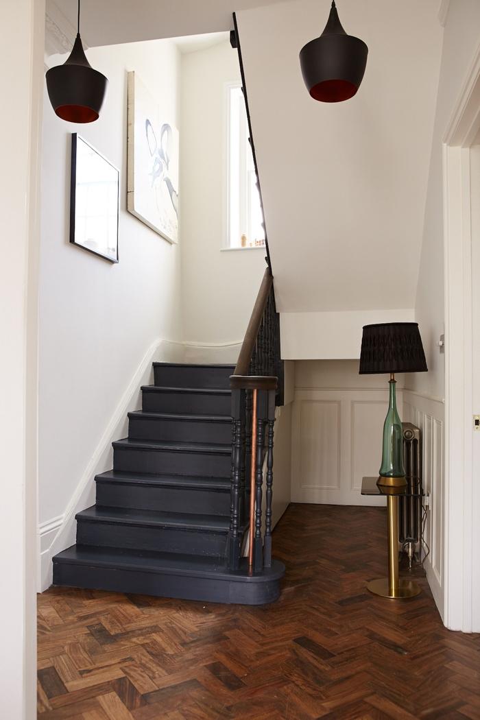 un escalier repeint en noir d'espace restreint en contraste avec l'intérieur blanc monochrome et l'ambiance scandinave épurée