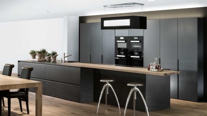 cuisine noir mat ouverte vers la salle à manger avec ilot central de forme rectangulaire longue à comptoir de bois