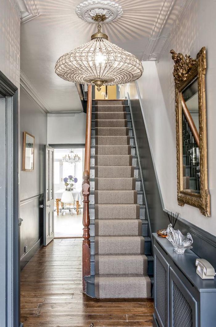 déco d'entrée élégante avec un escalier repeint en gris bleu accordé avec le lambris