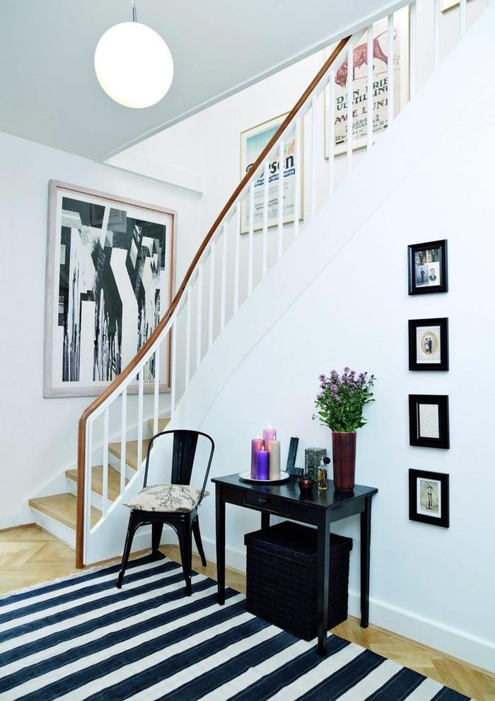 une galerie d'art aménagée dans une cage d'escalier étroite pour donner une touche arty dans le petit hall d'entrée en noir et blanc