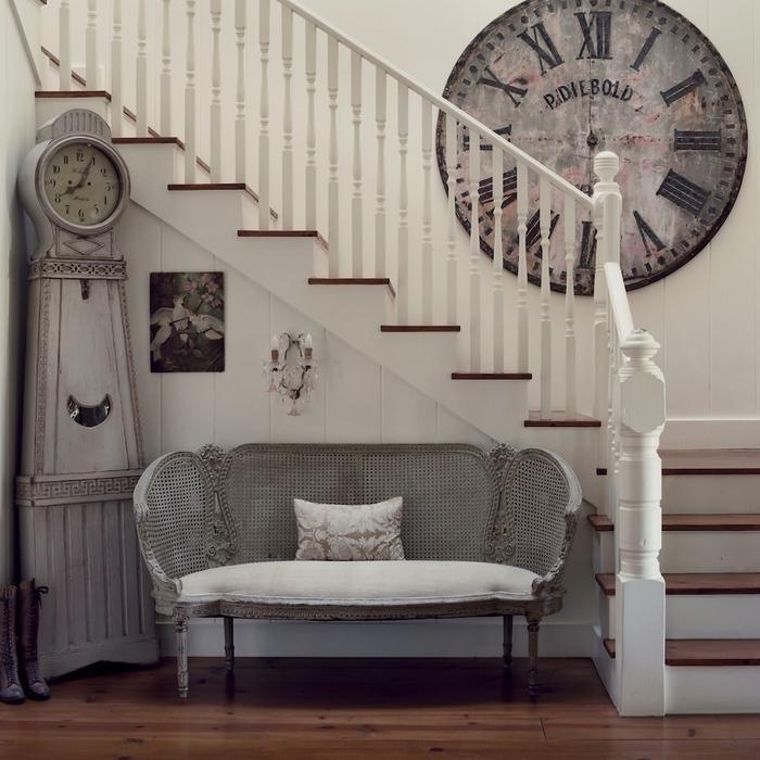 une cage d'escalier aménagée en style shabby chic et repeinte en blanc, grande horloge murale vintage qui apporte une touche de fantaisie à la montée d'escalier