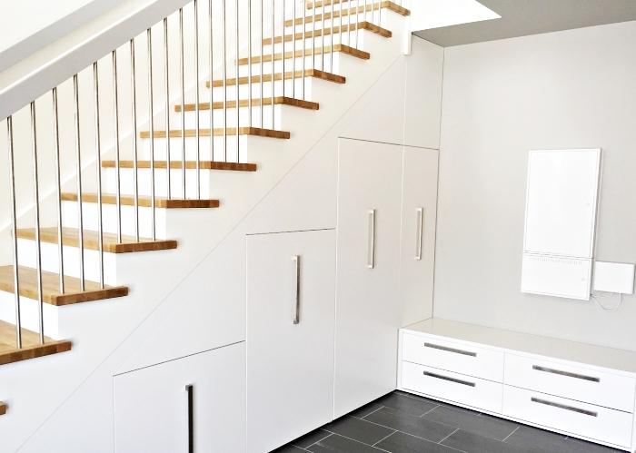couloir blanc au carrelage de plancher en gris anthracite avec meuble chaussure sous escalier de bois