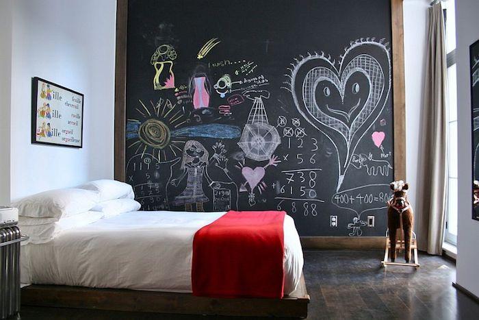 idée déco chambre enfant fille avec un mur en peinture ardoise avec des dessins originaux dessus, parquet marron, linge de lit blanc, couverture de lit rouge
