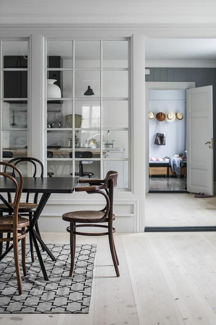 separateur de piece avec des verres, transparence et visibilité totale, tapis en forme carrée en gris et noir, chaises classiques en bois