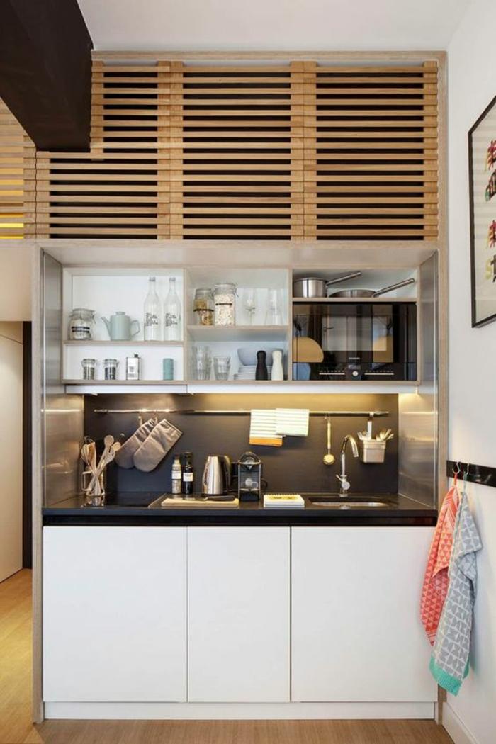 cuisine petit espace, avec des meubles insérés, sol recouvert de parquet PVC, plan de travail noir du meuble de l'évier