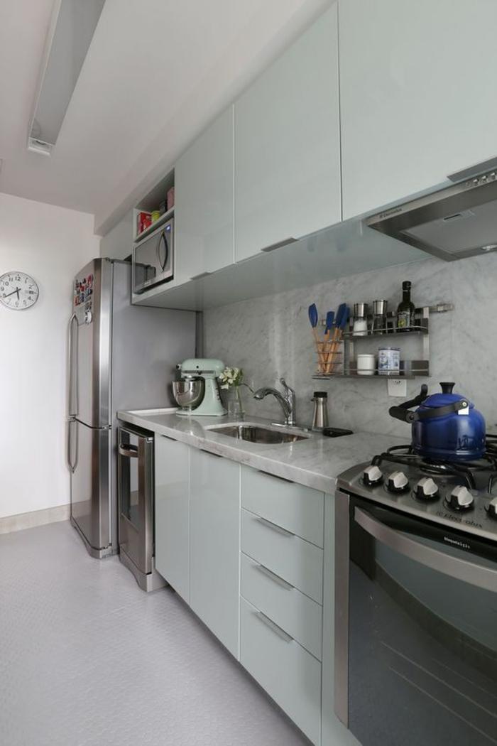 cuisine en longueur, petite cuisine, meubles en vert réséda, carrelage en gris clair, crédence aux motifs marbre, grand frigo en métal couleur argent, horloge de cuisine au mur