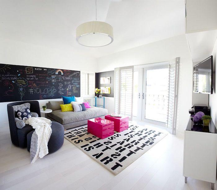 comment decorer un salon avec carré tableau ardoise noir avec des dessins et texte, canapé gris, fauteuil et tabouret gris anthracite, tables basses fuchsia, tapis à lettres noires