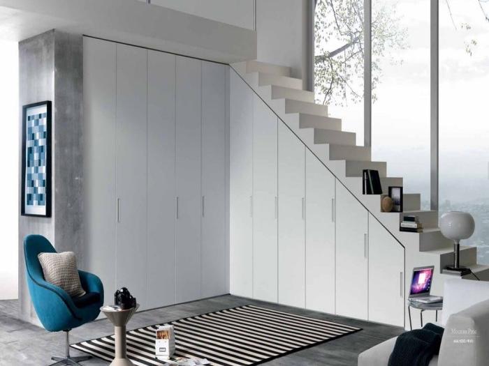 idée rangement sous escalier avec portes blanches, accessoires décoratifs tapis blanc et noir et coussin gris