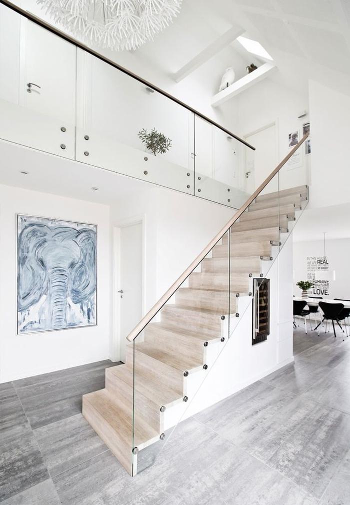 une ambiance de galerie d'art crée par l'habillage escalier en bois naturel, la rambarde en verre, la toile haute et le grand tableau accroché sous l'escalier