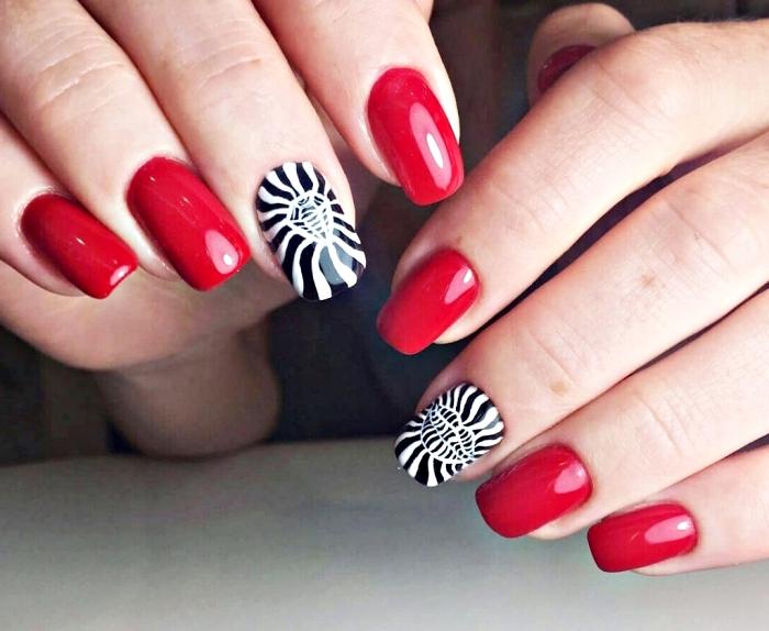 ongles mi longs en gel avec vernis rouge et décoration en blanc et noir à design diamant