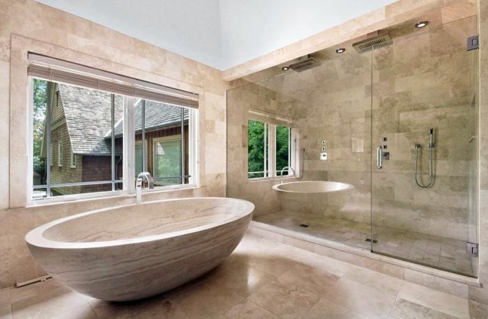 salle de bain luxueuse, baignoire travertin, grande fenêtre, miroir mural et cabine de douche