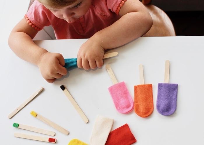 la pédagogie montessori en crèche, des batonnets de glace aux bouts colorés à faire correspondre à une housse colorée en feutrine