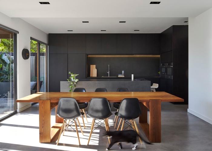 modèle de cuisine avec ilot central à design béton ouverte vers la salle à manger avec table rectangulaire en bois marron