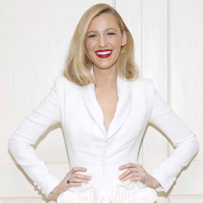 coupe de cheveux carré plongeant blond, cheveux lisses avec raie sur le coté, rouge à lèvres rouge, tailleur femme blanc
