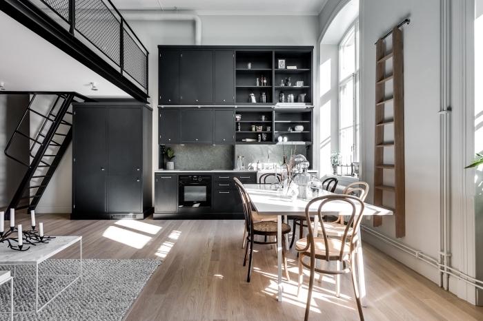 cuisine blanche avec armoires noires et plancher de bois stratifié, cuisine aménagée avec escalier noir moderne