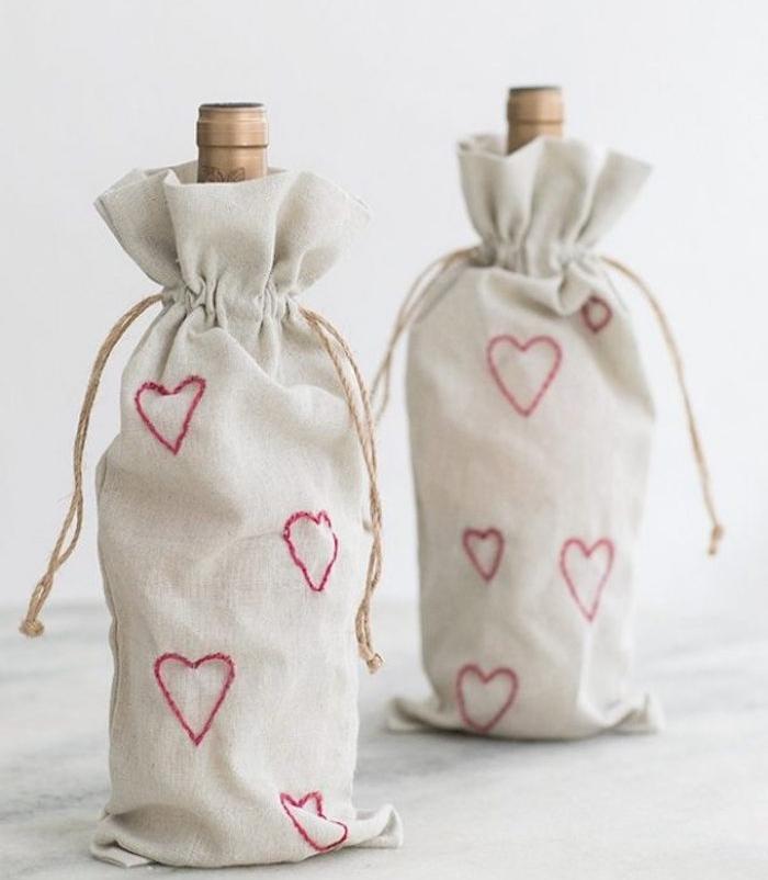 bouteilles de vin dans des petits sacs à bouteille blanc cassé avec motif coeur rouge cousu, cadeau saint valentin pour les amateurs du vin