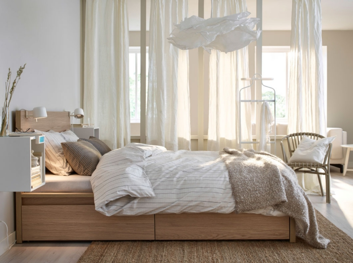 ambiance cozy dans la chambre à coucher adulte avec décoration en voiles longs de nuance écru et meubles en bois clair