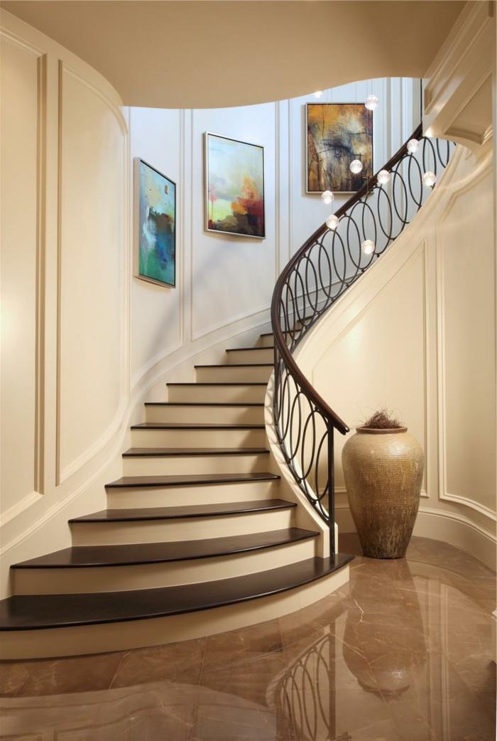 idées déco pour renover un escalier, montée d'escalier raffinée décorée de toiles élégante, avec un garde-corps en fer sculpté