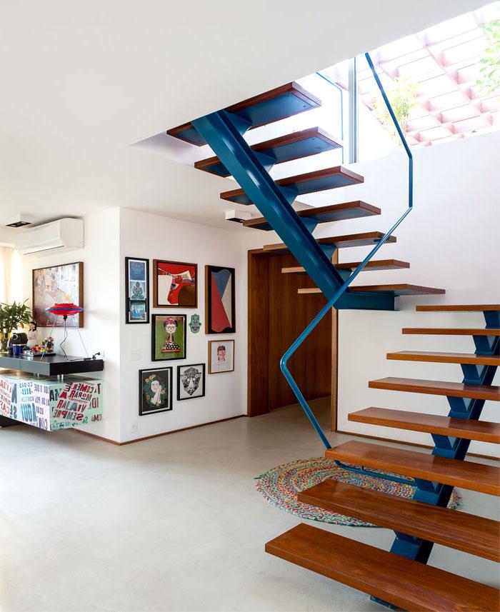 cage d'escalier d'esprit loft avec un limon métallique repeint en bleu supportant les marches en bois