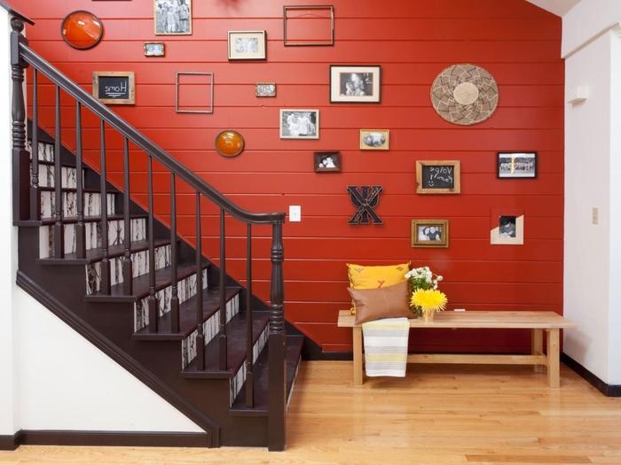 une cage d'escalier aux couleurs contrastées agrémentée d'une galerie murale, lambris rouge tonique qui fait ressortir l'escalier en blanc et marron