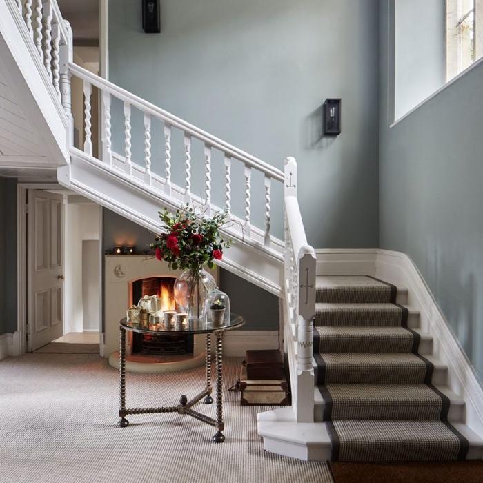 escalier repeint en blanc à l'ancienne en harmonie avec un pan de mur en gris bleu