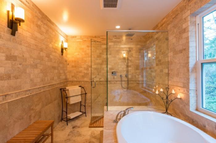 pierre travertin, baignoire blanche, murs en pierre naturelle beige, appliques murales