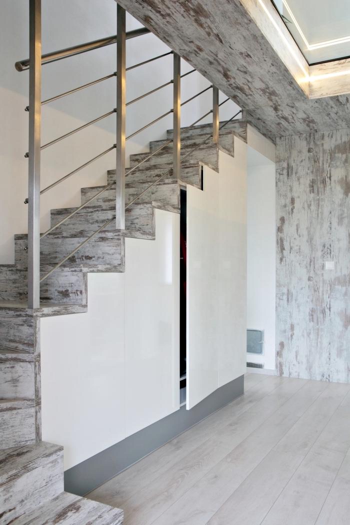 intérieur aux murs blancs avec revêtement de bois gris sur l'escalier et un amenagement sous pente