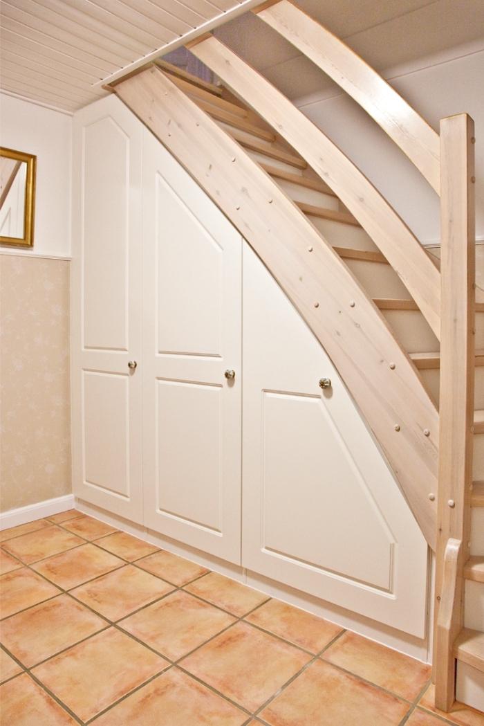 comment optimiser l'espace limité avec un aménagement sous escalier de bois peint en blanc