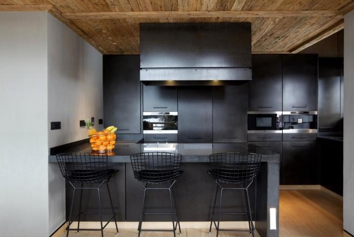 cuisine aux armoires noires avec plafond en bois foncé massif, cuisine aménagée avec ilot central noir