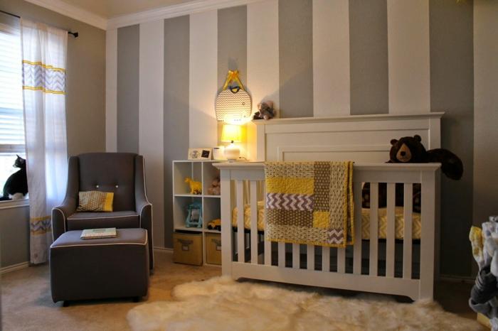 chambre de bébé, fauteuil gris, tapis fourrure blanche, mur en gris et blanc