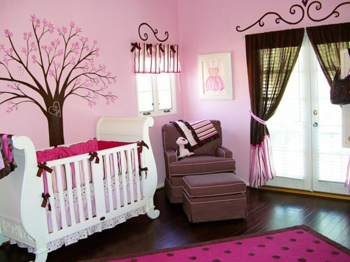 chambre bébé fille, tapis pourpre, fauteuil marron, peinture murale rose