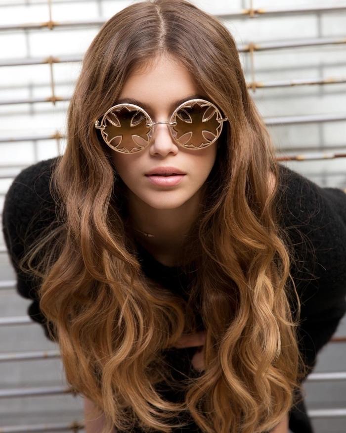 couleur de cheveux, jeune femme aux cheveux longs et bouclés de nuance base châtain et pointes dorées