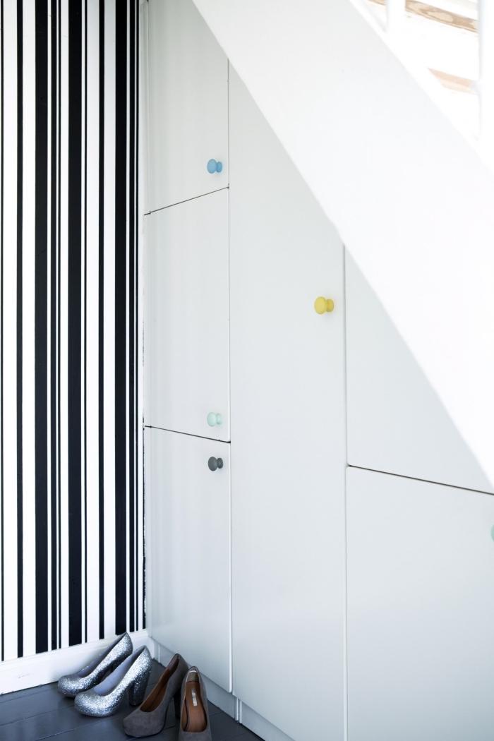 modèle de placard sous escalier à design blanc avec poignées en couleurs différentes pour stocker les chaussures