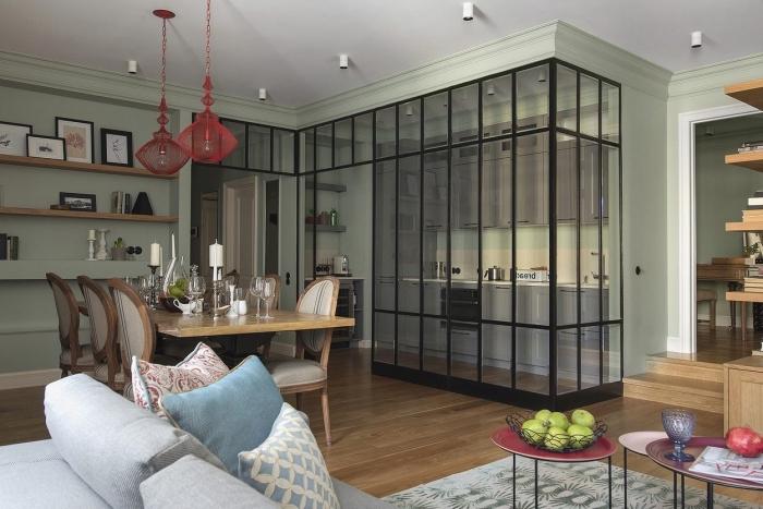 separation cuisine salon, pièce ouverte aux murs verts avec parquet de bois, cuisine ouverte avec séparation en verre