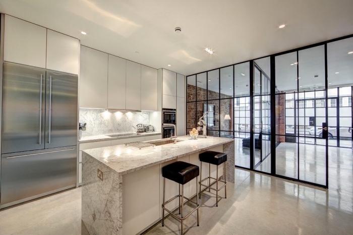 cloison vitrée, déco de cuisine blanche et moderne avec meubles sans poignées et comptoir à design marbre de luxe