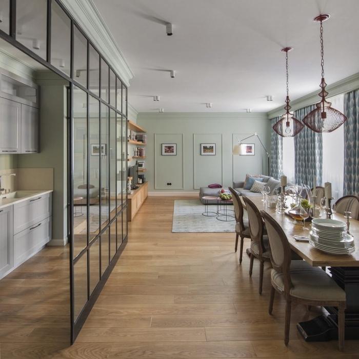 cuisine ouverte avec verrière, salle à manger et salon aux murs vert pastel et plafond blanc avec lampes suspendues violet