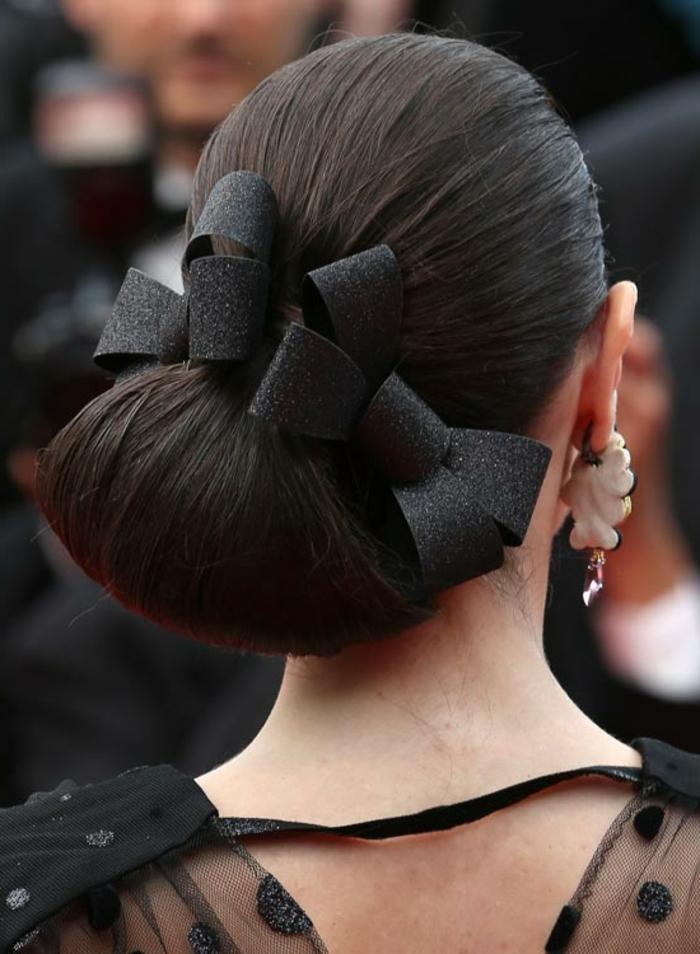grands boucles d'oreille, accessoires noirs dans les cheveux, chignon bas, coiffure demoiselle d'honneur