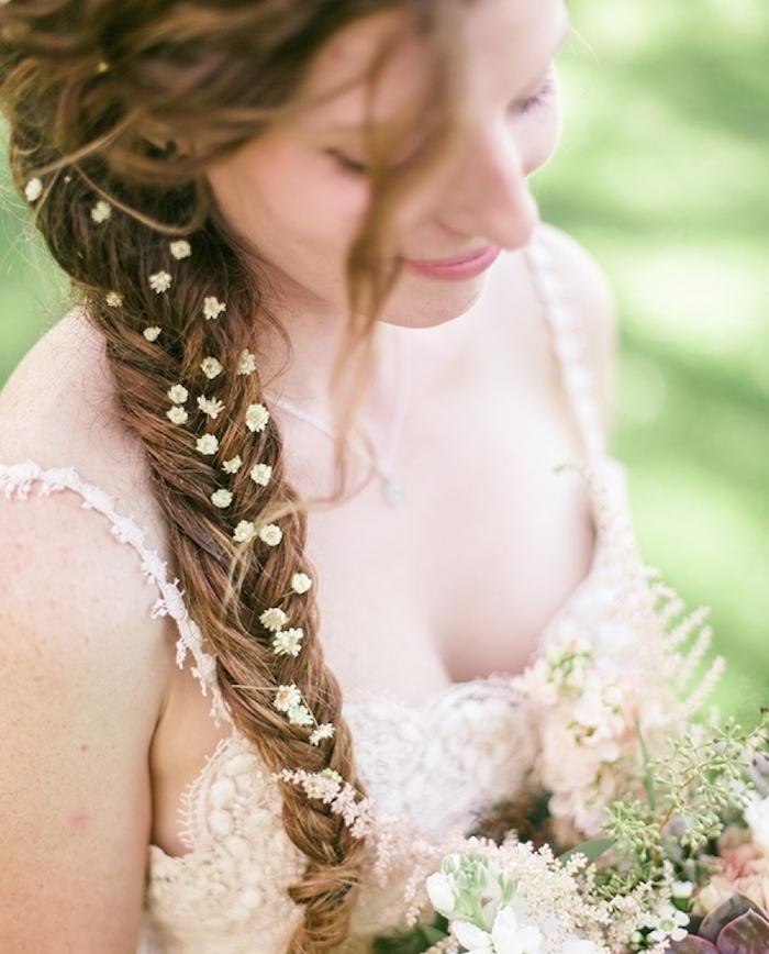 modele de coiffure tresse épi sur le coté style boheme chic avec des mèches rebelles et petites fleurs dans les cheveux, robe de mariée champêtre